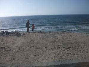 Ayah dan anak di tepi laut Mediterrania, Gaza