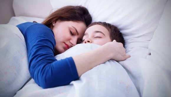 Mother and son lay in bed together